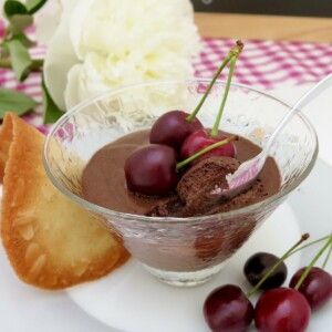 glass dish of chocolate mousse with cherries